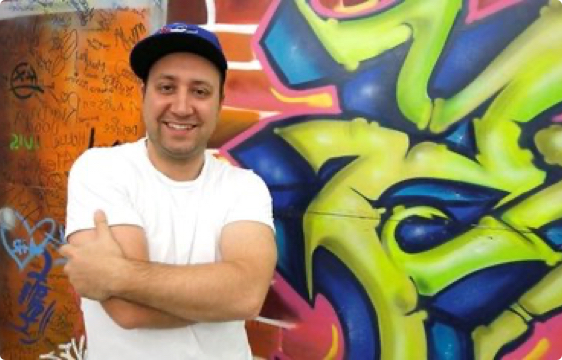Michael Falcucci poses in front of a wall with graffiti