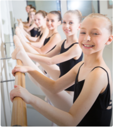 A group of young girls in a ballet class doing barre work